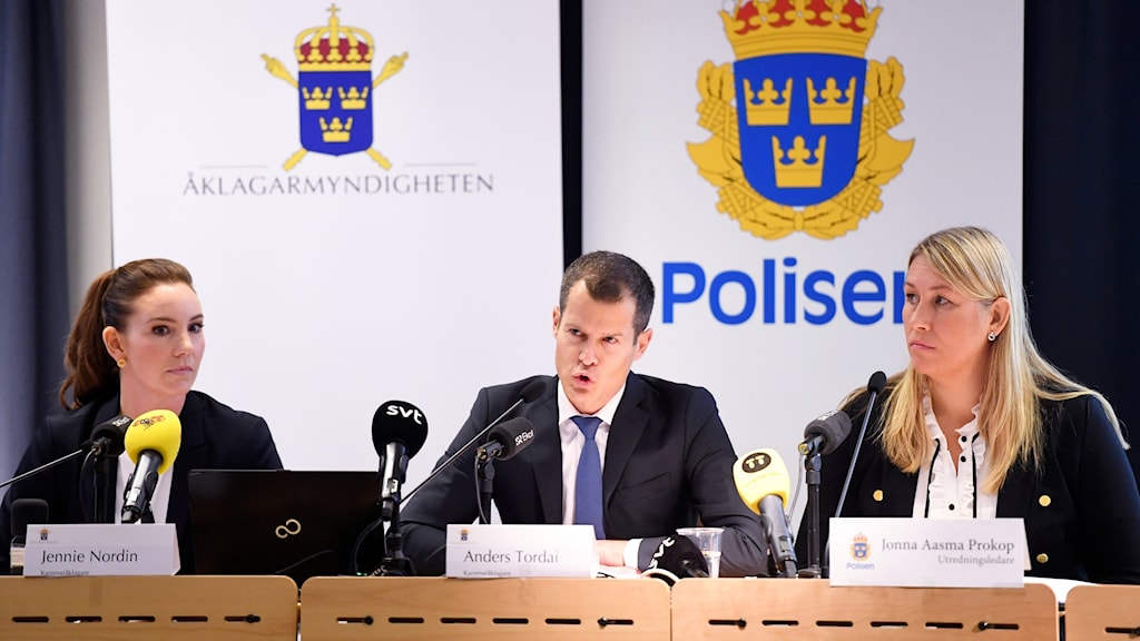 Three prosecutors behind a desk at a press conference.