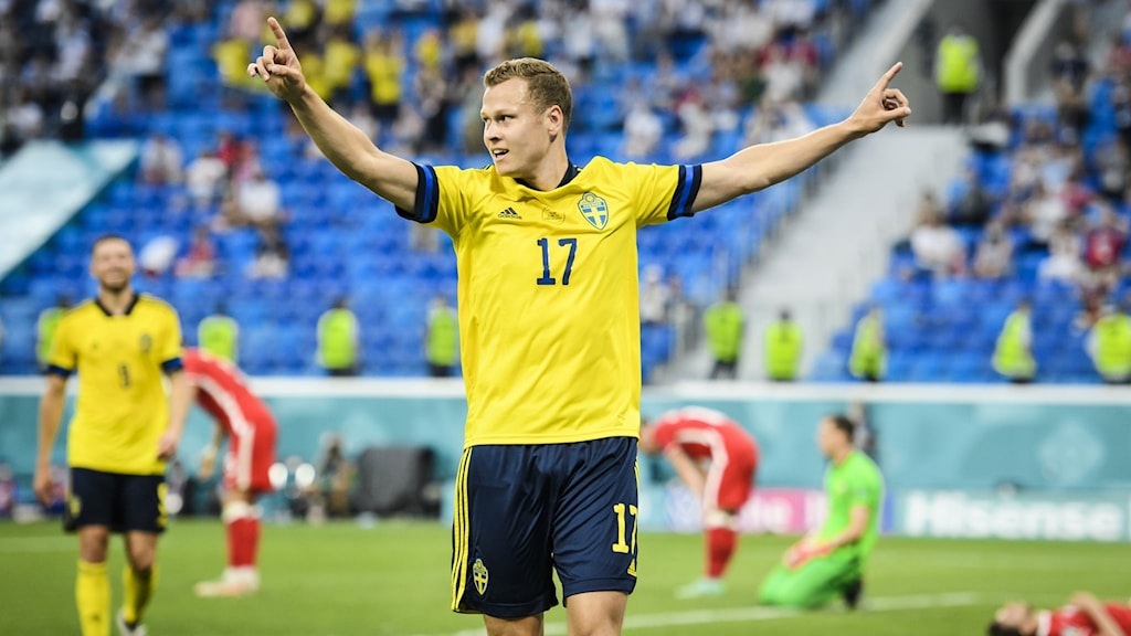 An image of a football player with arms outstretched celebrating.