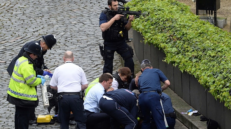 Police and security reacting to attack in London. One officer has his gun drawn.