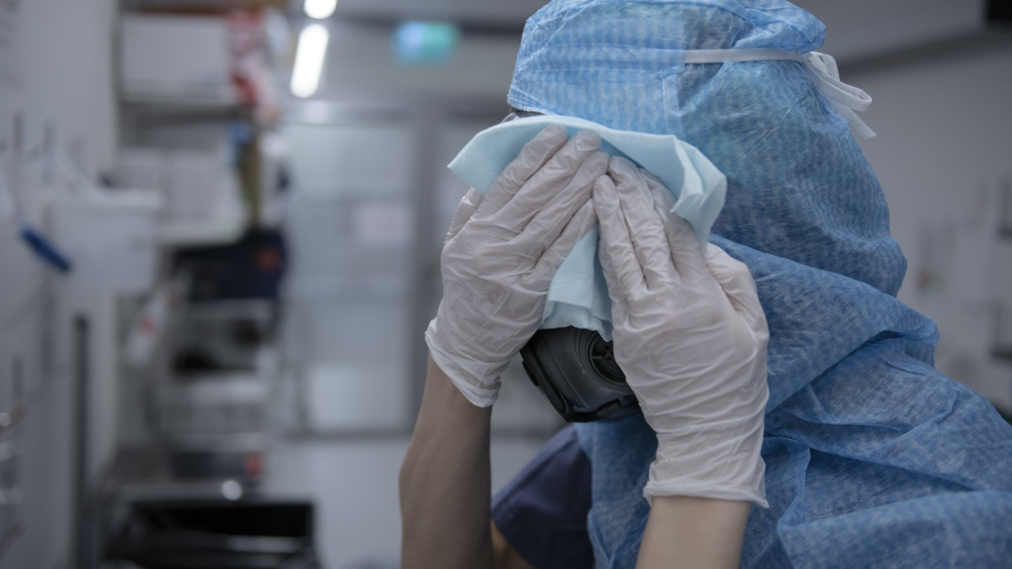 ICU staff in protective gear drying off the face shield.
