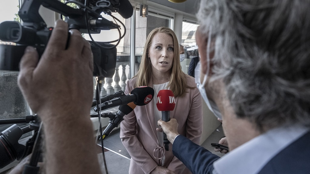 A woman surronded by media microphones and cameras