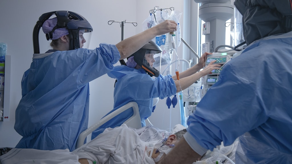 An image of nurses in full PPE caring for someone in a hospital bed.