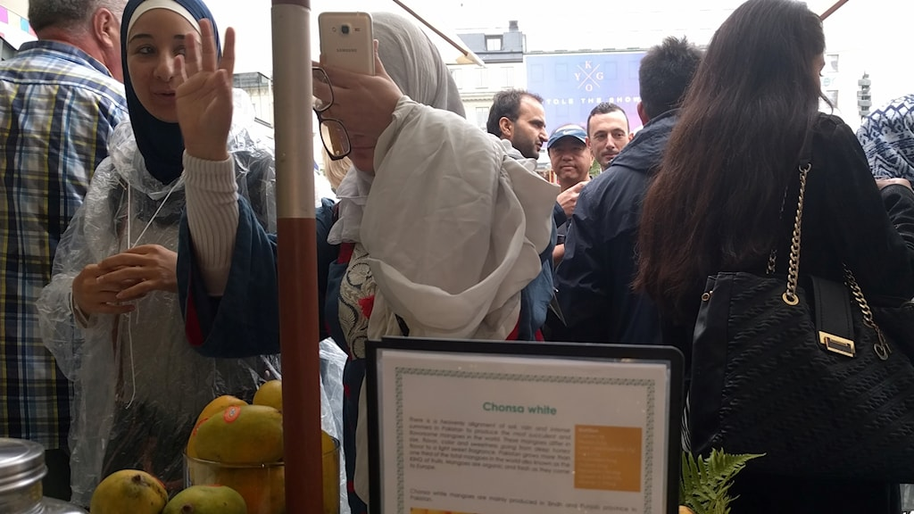 Mala Galal Fayed from Egypt and her friend Alia Amir taste mangoes at the festival.