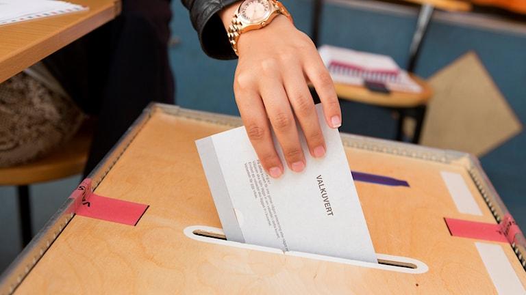 Han placing a ballot in a ballot box.