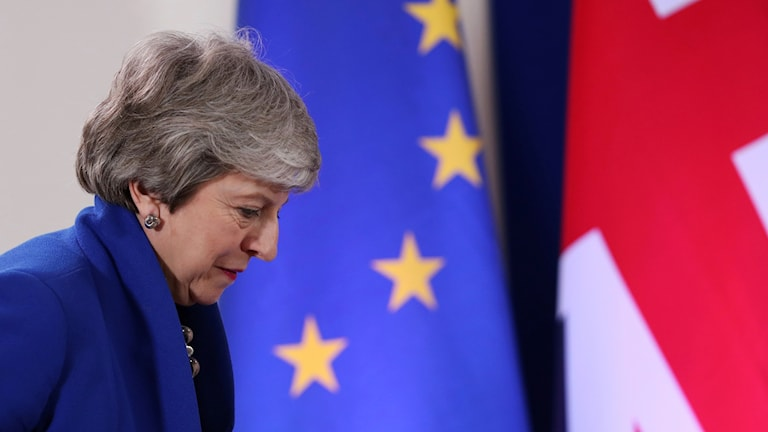 Woman in passing the EU and British flags.