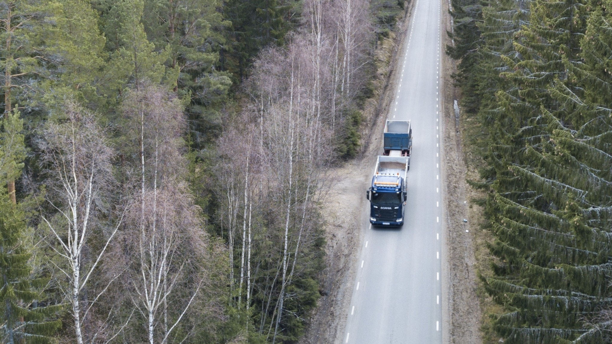 Aerial of a rural road with a lorry on it.