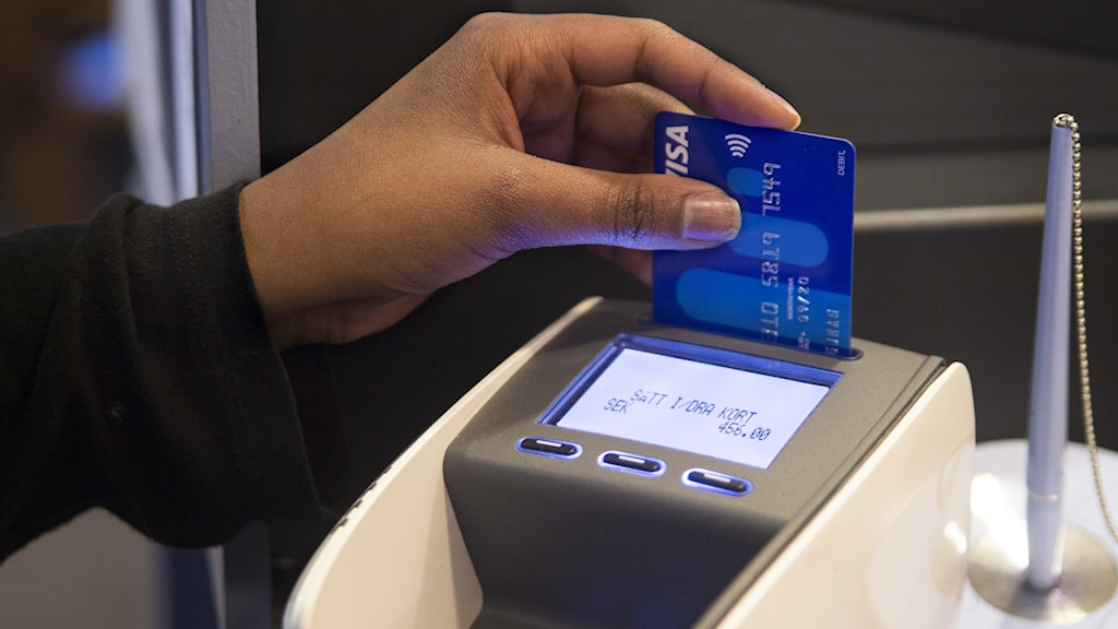 A person paying using a card reader.