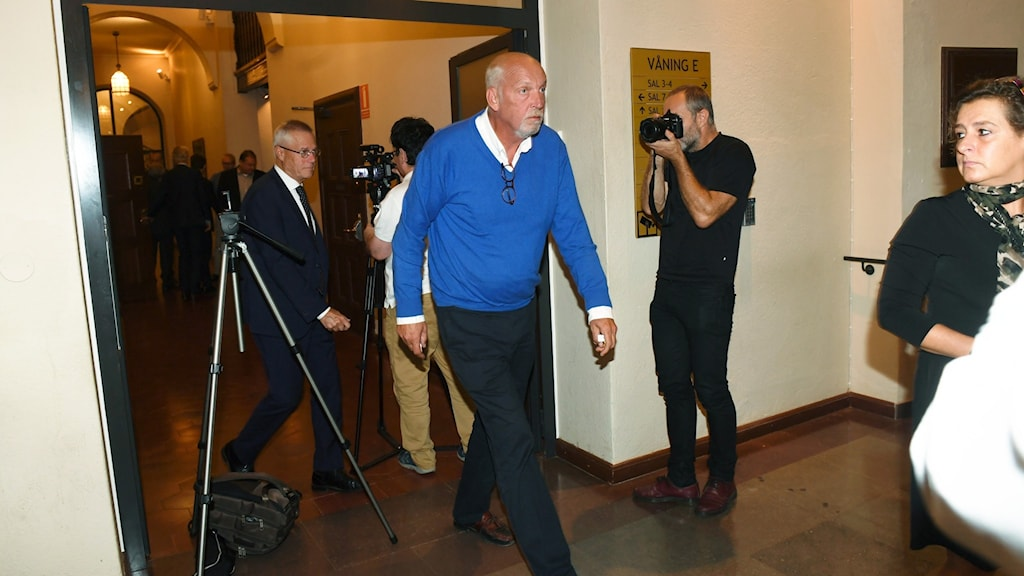 A man in a blue sweater walking in a hallway with photographers.