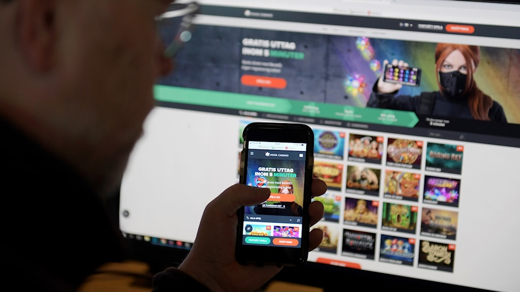Man with a phone in front of an online casino ad.