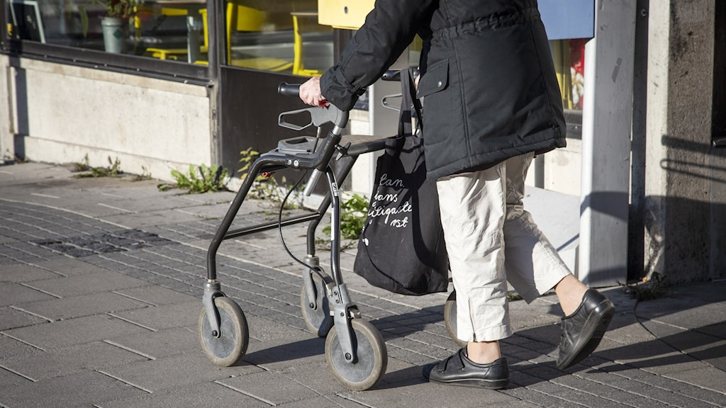 A person walking down a street with a walking frame on wheels.