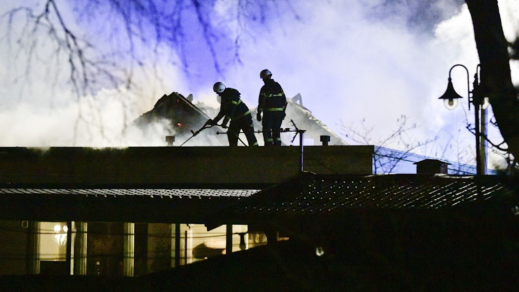 A night scene showing firefighters on top of a building wreathed in smoke.