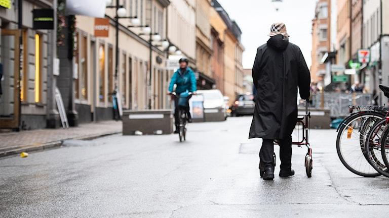 An elderly woman walking down a city sidewalk.