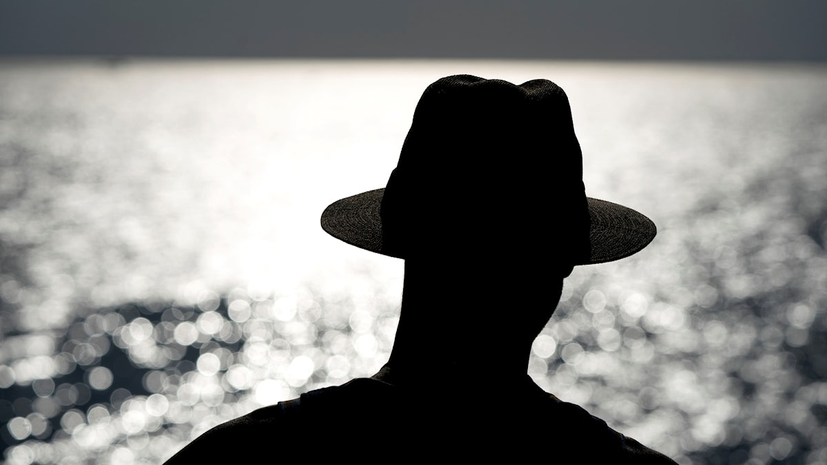 A sillhouette of a person wearing a hat in the heat