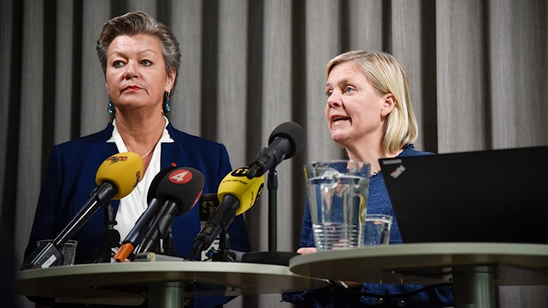 two women with several news microphones in front of them