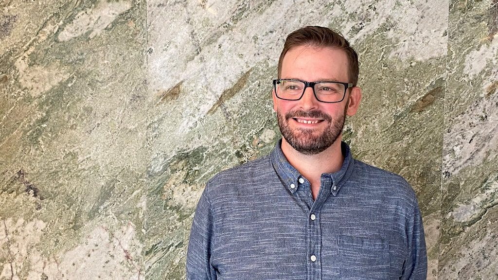 Man, smiling, in front of a stone wall.