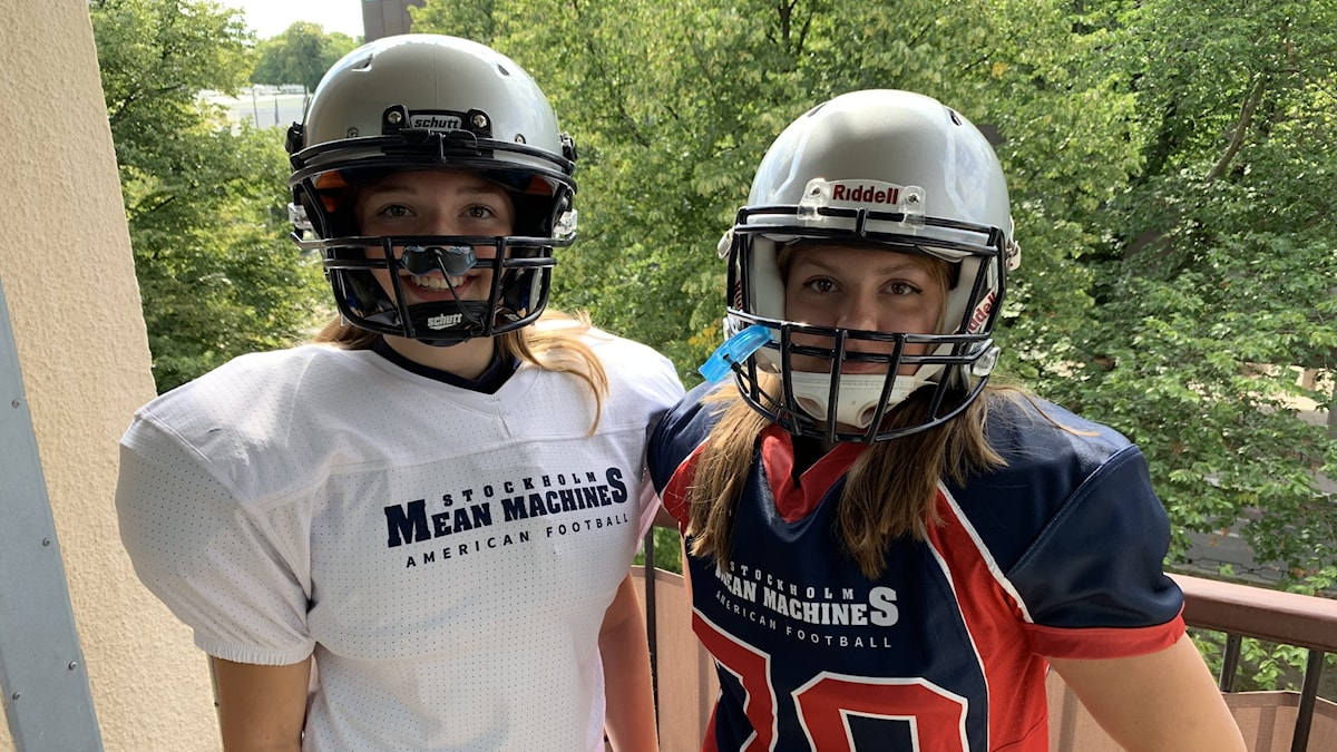 Two girls outdoors in American football gear and helmets