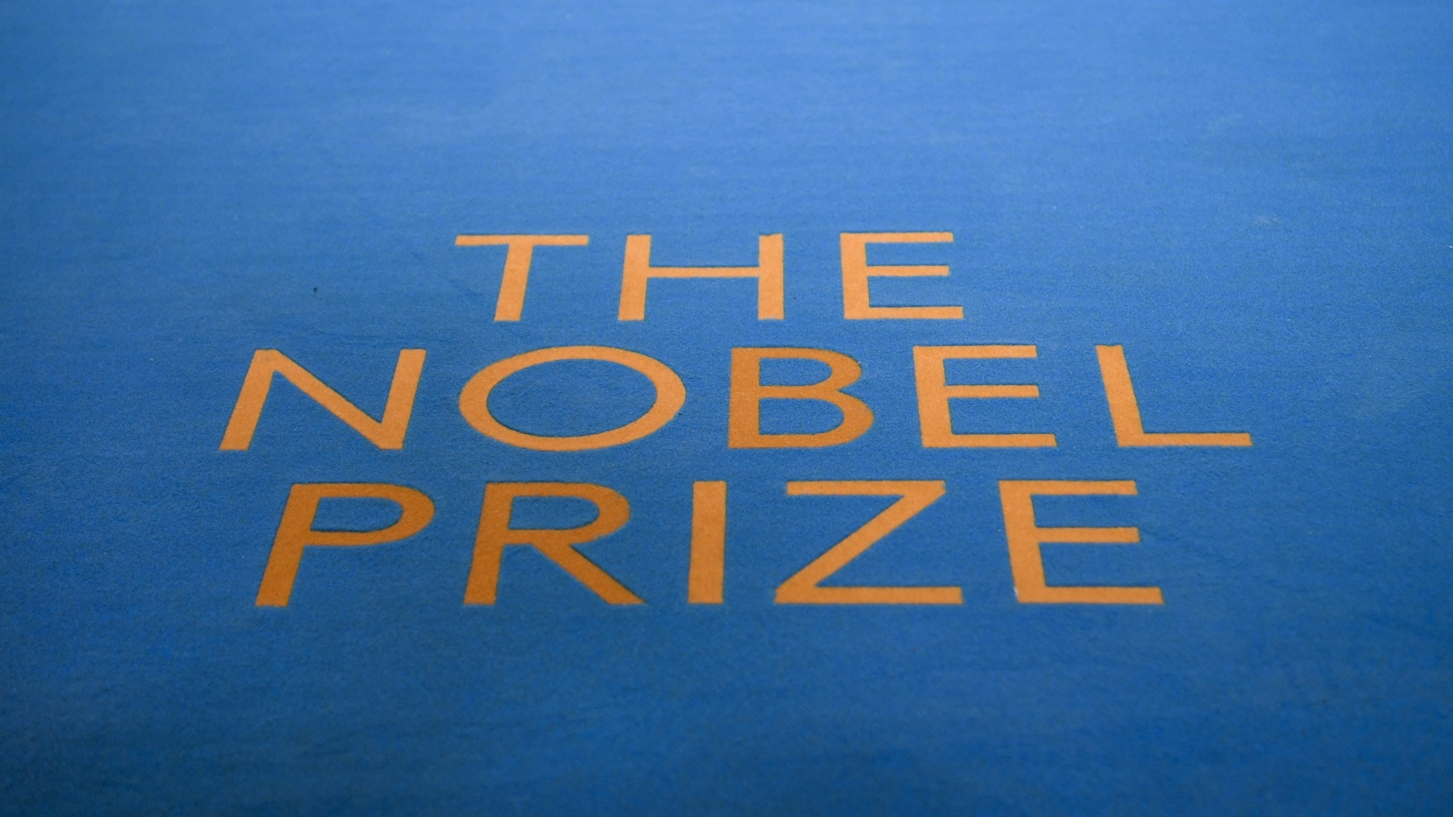 """The words """"the nobel prize"""" on a blue carpet."""