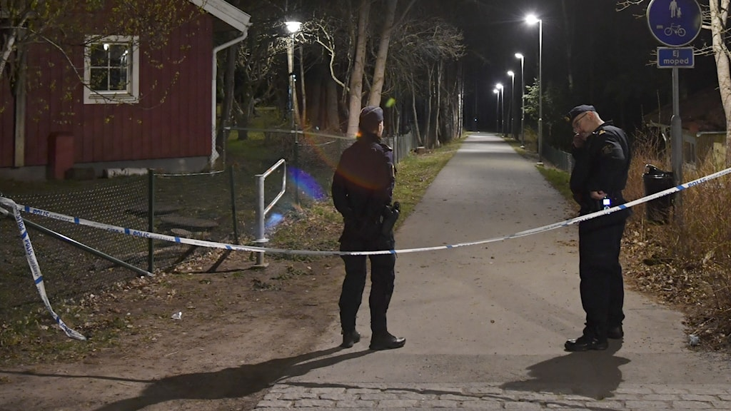 An image of two police officers out on a lighted path at night.