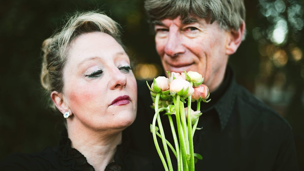 A man and a woman standing outside and holding flowers.