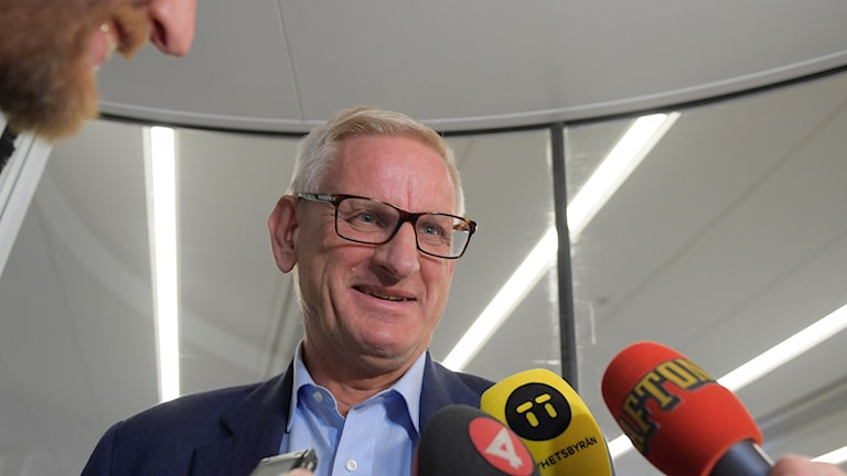 Former Prime Minister Carl Bildt answers questions while trapped in a revolving door outside the Expressen newspaper.