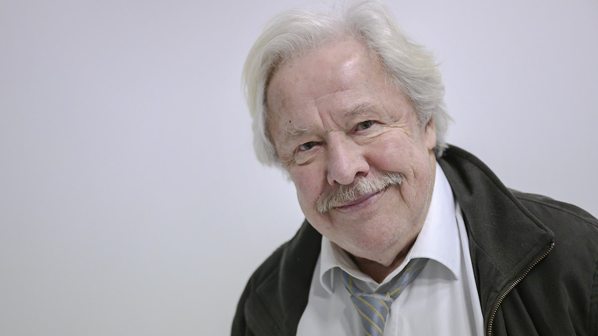 An elderly man with a mustache smiling into the camera.