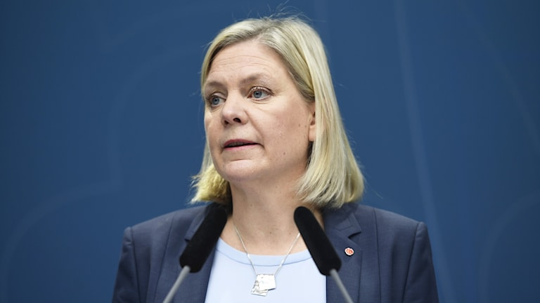 Sweden's finance minister, Magdalena Andersson, stands behind two microphones.