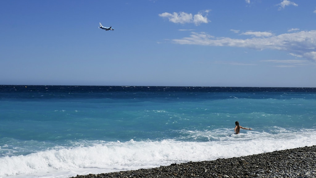 Picture of an airplane in the sky above a beach in the Mediterranean.