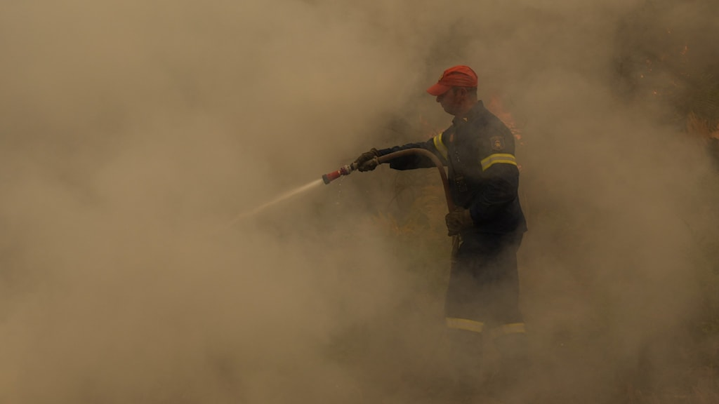 a firefighter surrounded by something that looks like amber-colored fog.