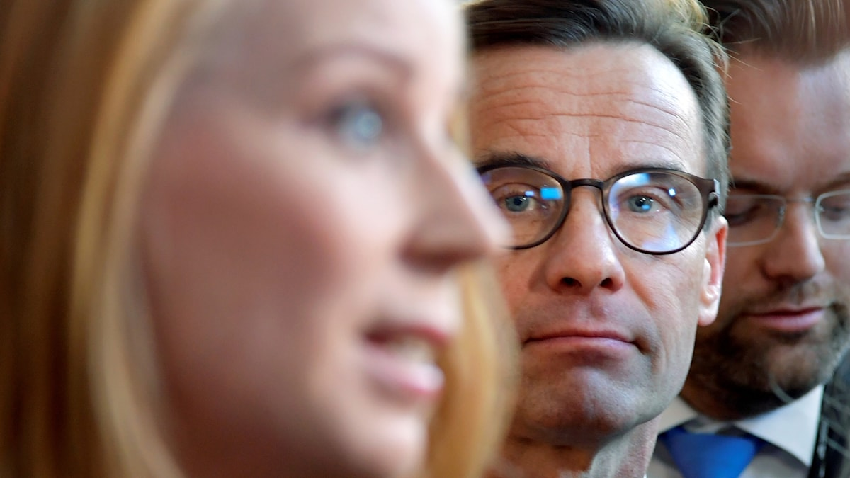 A blurred portrait photo of Annie Lööf, with Ulf Kristersson behind her.