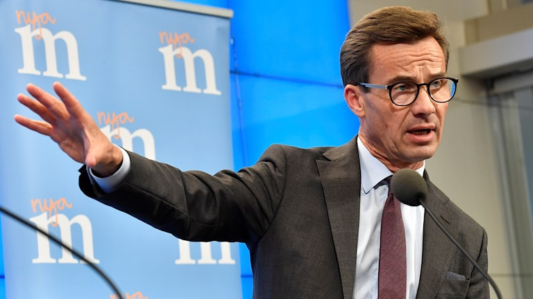 Man in glasses by a microphone, gesturing