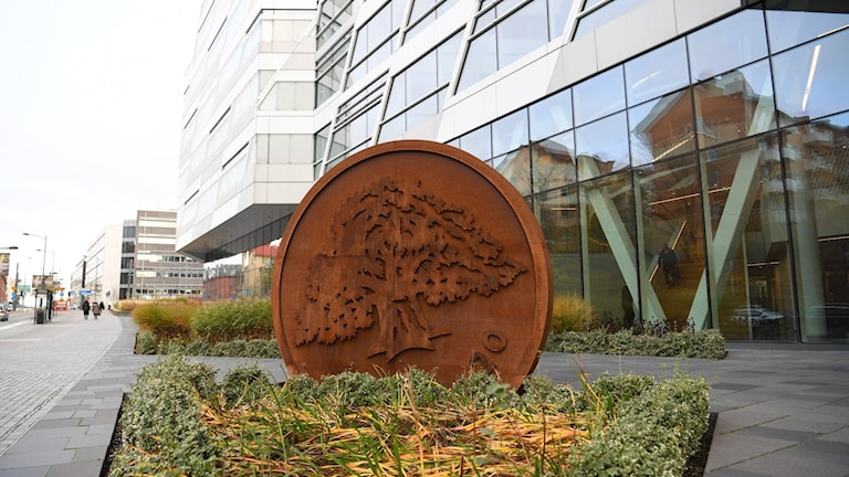 Swedbank logo as a sculpture - a coin with a tree on it- outdie a classed building.