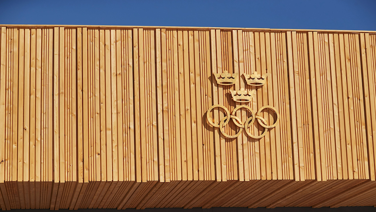 The Olympic rings and three crowns on a wall.