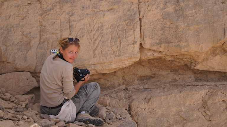 Archeologist Maria Nilsson in front of the stone carving. Photo: Private