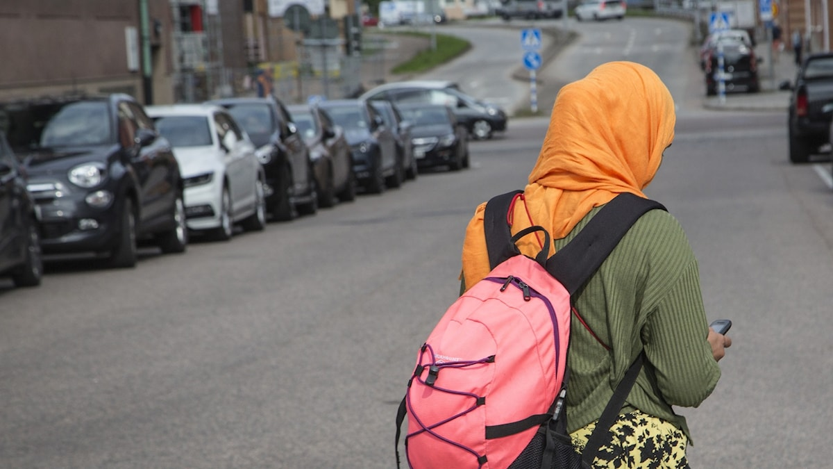 The back of a girl wearing a backpack and a veil.