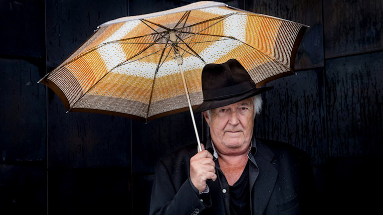 Author Henning Mankell stranding indoors carrying a yellow umbrella. Photo: Nora Lorek / TT