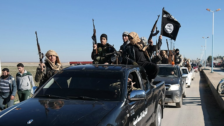 Islamic State militants pass by a convoy in Tel Abyad, northeast Syria. File Photo: AP.