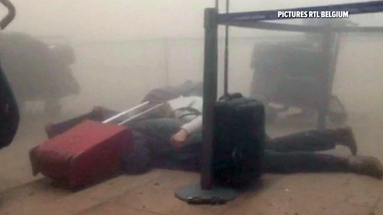 A still image taken from video from RTL Belgium showing unidentified travellers lie on the floor in a smoke filled terminal at Brussels Airport. Photo: AP / RTL.