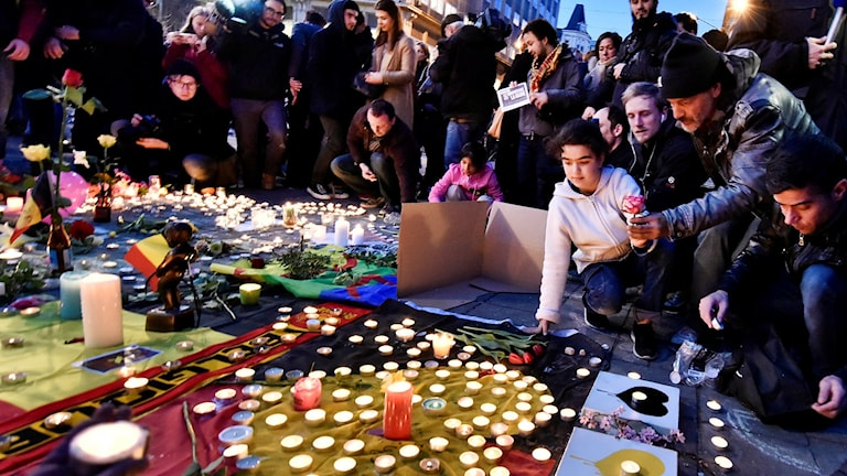 People bring flowers and candles to mourn for the victims at Place de la Bourse in the center of Brussels. Photo: Martin Meissner / AP.