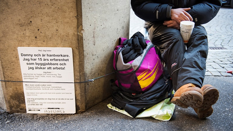 Person begging with a mug between his legs and a sign to explain his situation.