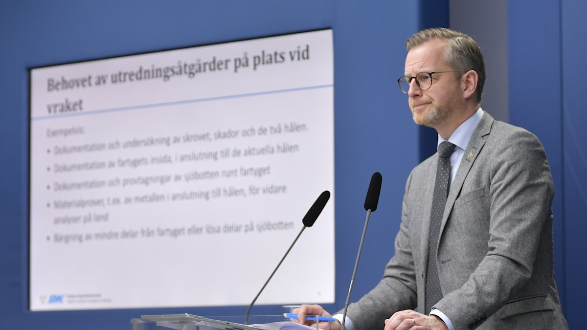 Home affairs minister Mikael Damberg standing in front of a screen.