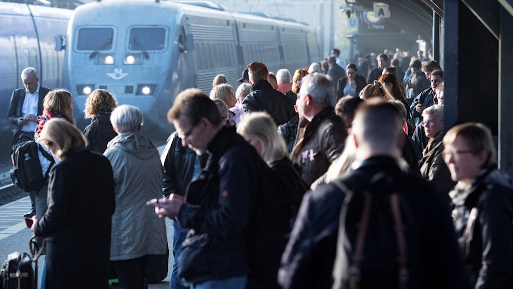 Passengers at a train station, waiting for a delayed train.