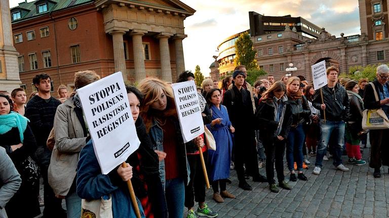 """Människor demonstrerar. en skylt säger """"Stoppa polisens rasistiska register""""."""