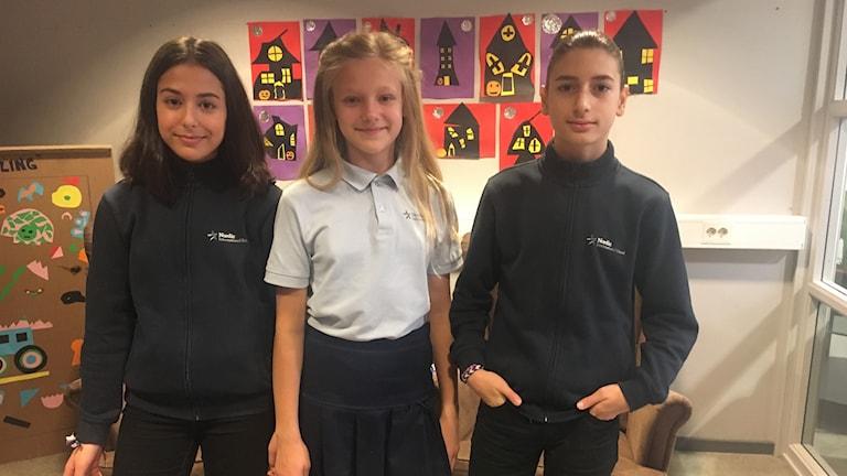 Three kids in a school uniform.