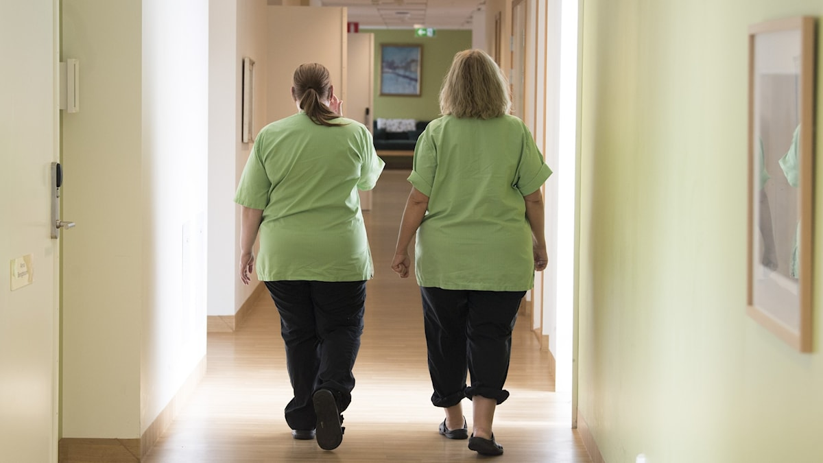 Two nurses walking in a corridor.