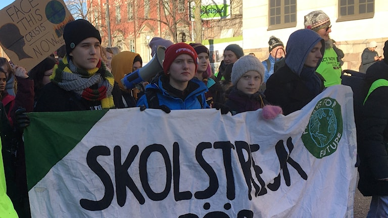 Youngster walking outside holding a giant side that reads skolstrejk.