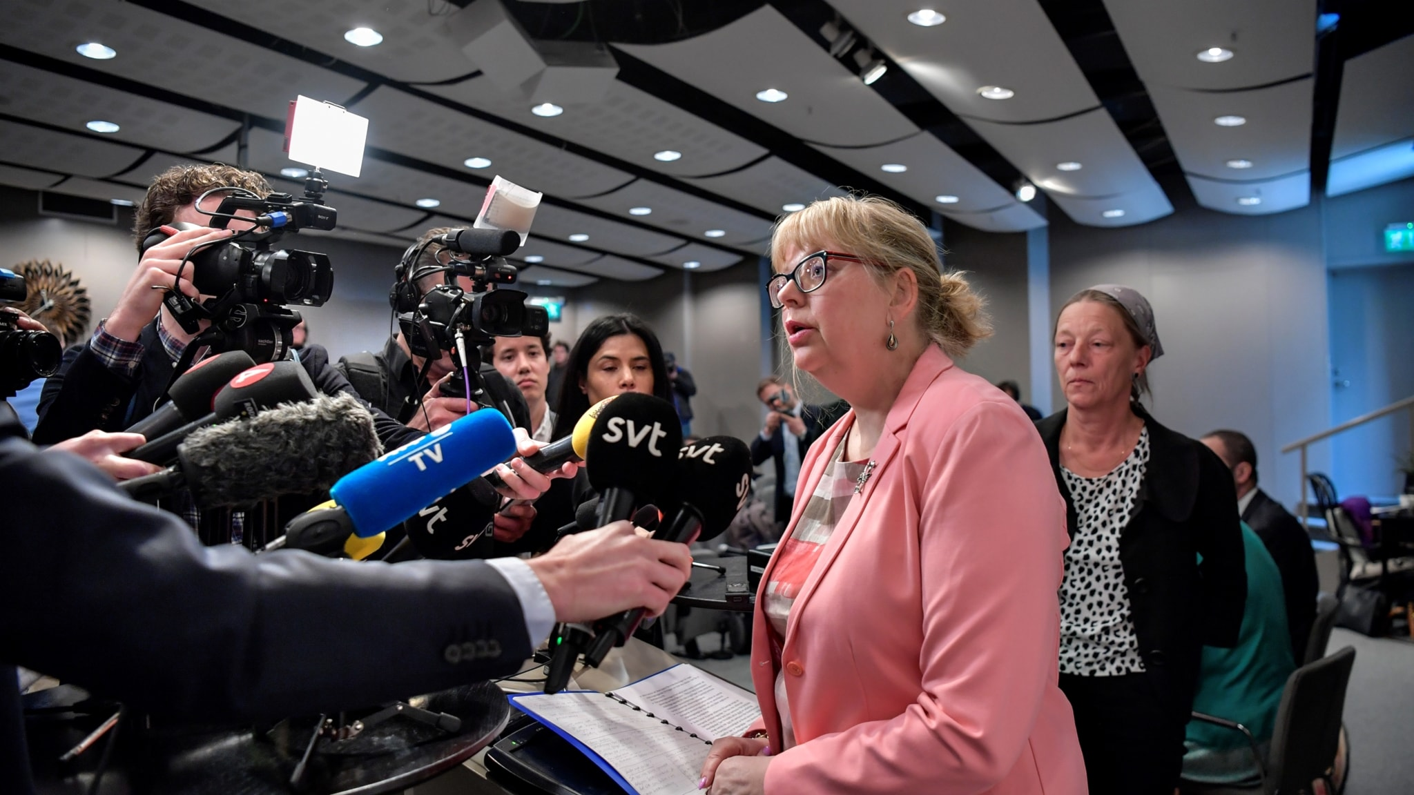 A woman in glasses speaking into mics held by reporters.