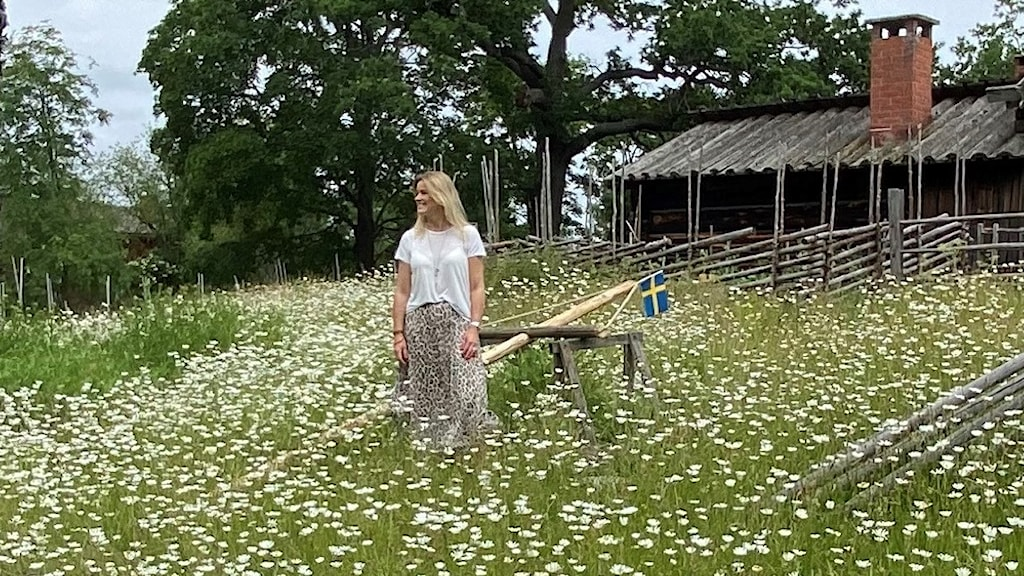 """Woman in a field, surrounded by daisies, by a maypole that still has not been """"dressed""""."""