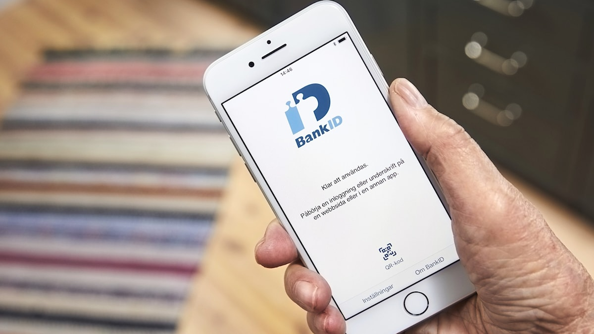 A person holding a phone displaying the app bank-id.