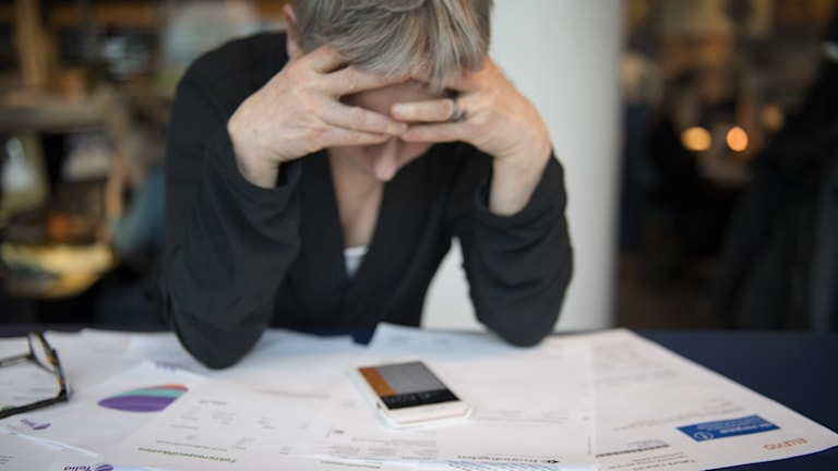 A picture of a person holding their head in their hands as they look at a pile of bills.