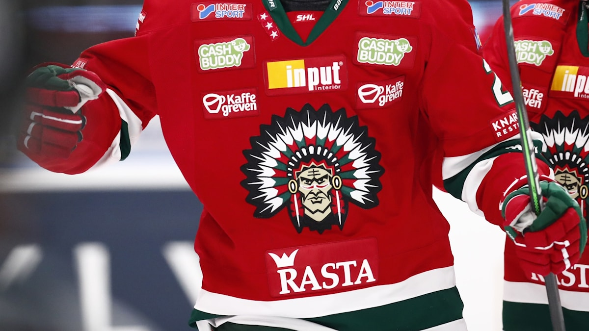 A hockey player wearing a jersey with a native American in a feather headdress on it.